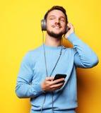 Bärande hörlurar för ung man och innehavmobiltelefon royaltyfri fotografi