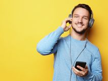 Bärande hörlurar för ung man och innehavmobiltelefon arkivbild