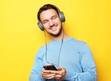 Bärande hörlurar för ung man och innehavmobiltelefon royaltyfria bilder