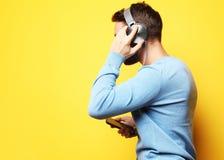 Bärande hörlurar för ung man och innehavmobiltelefon royaltyfri bild