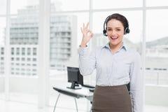 Bärande hörlurar med mikrofon för affärskvinna, medan göra en gest ok underteckna in kontoret Arkivfoton