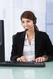 Bärande hörlurar med mikrofon för affärskvinna på datorskrivbordet Royaltyfri Fotografi