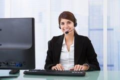Bärande hörlurar med mikrofon för affärskvinna på datorskrivbordet Royaltyfri Foto