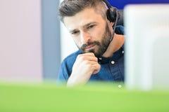 Bärande hörlurar med mikrofon för fundersam mitt- vuxen affärsman på kontoret arkivbild