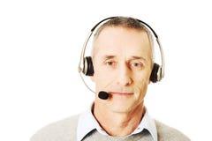 Bärande hörlurar med mikrofon för gammal man för appellmitt Royaltyfri Foto