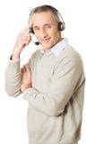 Bärande hörlurar med mikrofon för gammal man för appellmitt Fotografering för Bildbyråer