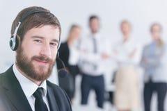 Bärande hörlurar med mikrofon för kontorsarbetare arkivfoton