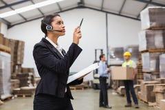 Bärande hörlurar med mikrofon för lagerchef som kontrollerar inventarium Arkivbilder