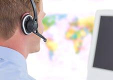 Bärande hörlurar med mikrofon för resebyråmanman framme av världskartan arkivfoto