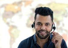 Bärande hörlurar med mikrofon för resebyråmanman framme av världskartan royaltyfri foto