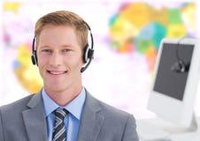 Bärande hörlurar med mikrofon för resebyråmanman framme av världskartan royaltyfri bild