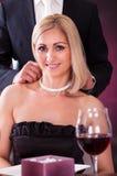 Bärande halsband för man till kvinnan i restaurang arkivfoto