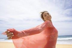 Bärande halsdukanseende för bekymmerslös kvinna på stranden Fotografering för Bildbyråer