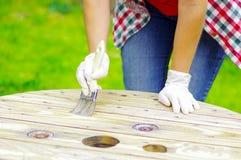 Bärande handskar för kvinna som gör ren en wood tabell med en borste Royaltyfri Fotografi