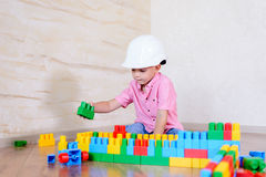 Bärande hardhat för ung pojke som inomhus spelar Fotografering för Bildbyråer