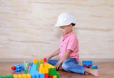 Bärande hardhat för ung pojke som inomhus spelar Royaltyfria Foton