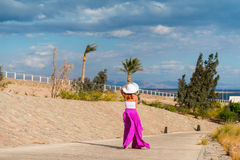 Bärande hatt för härlig kvinna och rosa färgkjol Arkivfoto