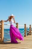 Bärande hatt för härlig kvinna och rosa färgkjol Fotografering för Bildbyråer