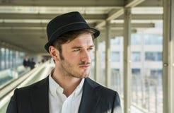 Bärande hatt för man och se ut fönstret arkivfoto