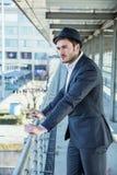 Bärande hatt för man och se ut fönstret Arkivfoton