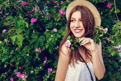 Bärande hatt för ung hipsterflicka som går vid blommande rosor Kvinnan tycker om blommor parkerar in Sommardräkt arkivfoton