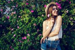 Bärande hatt för ung hipsterflicka som går vid blommande rosor Kvinnan tycker om blommor parkerar in Sommardräkt royaltyfria bilder