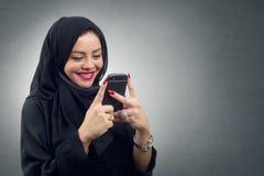 Bärande hijab för arabisk dam genom att använda hennes mobil, Arkivbilder