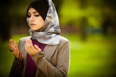 Bärande hijab för härlig muslimkvinna som ber på radbandet/tespih Royaltyfri Foto