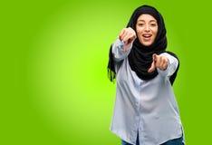 Bärande hijab för ung arabisk kvinna som isoleras över grön bakgrund arkivbild