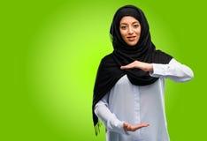 Bärande hijab för ung arabisk kvinna som isoleras över grön bakgrund royaltyfria bilder