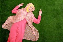 Bärande hijab för ung muslimkvinna som ligger på gräs Arkivbilder