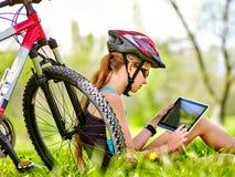 Bärande hjälm för cykelflicka som sitter nära minnestavlan för cykelklockaPC Royaltyfri Bild