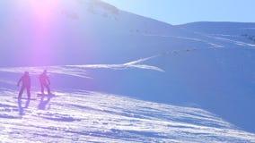 Bärande hjälm för Sportive folk och maskering i sportkläder, snowboarding från snöig berglutning arkivfilmer