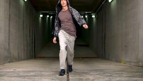 Bärande hoodie för ung huliganstreetstylegrabb i en flyttning, medan gå från parkeringen stock video