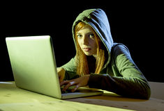 Bärande huv för ung attraktiv tonårig kvinna på begrepp för brott för cyber för cybercrime för dataintrångbärbar datordator Arkivbilder