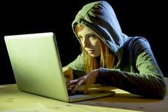 Bärande huv för ung attraktiv tonårig kvinna på begrepp för brott för cyber för cybercrime för dataintrångbärbar datordator Royaltyfri Bild