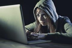 Bärande huv för ung attraktiv tonårig kvinna på begrepp för brott för cyber för cybercrime för dataintrångbärbar datordator Arkivfoto