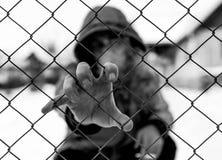 Bärande huv för Unidentifiable caucasian man och att röka cigaretten som rymmer trådstaketet fotografering för bildbyråer