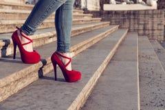 Bärande jeans för kvinna och röda skor för hög häl i gammal stad De höga hälen för kvinnakläder går på trappa Sexiga ben i röd hö Royaltyfria Bilder