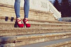 Bärande jeans för kvinna och röda skor för hög häl i gammal stad De höga hälen för kvinnakläder går på trappa Sexiga ben i röd hö Arkivbild