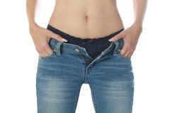 Bärande jeans för kvinnlig och isolerat på den vita backgroen Fotografering för Bildbyråer