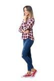 Bärande jeans för ursnygg gatastilkvinna, plädskjorta och gymnastikskor som ler att se ner Arkivfoto