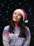 Bärande jul tröja och Santa Hat för asiatisk flicka på mörkt glöd arkivfoto