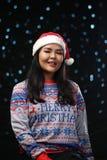 Bärande jul tröja och Santa Hat för asiatisk flicka på mörkt glöd arkivfoton