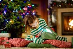 Bärande julpyjamas för lycklig liten flicka som öppnar en gåvaask vid en spis i en hemtrevlig mörk vardagsrum på julhelgdagsafton arkivbild