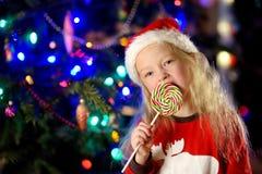 Bärande julpyjamas för lycklig liten flicka som har den enorma randiga julklubban i en hemtrevlig mörk vardagsrum på julhelgdagsa Arkivbilder