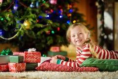Bärande julpyjamas för lycklig liten flicka som spelar vid en spis i en hemtrevlig mörk vardagsrum på julhelgdagsafton royaltyfria foton