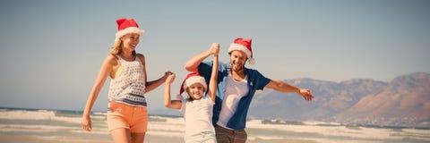 Bärande jultomtenhatt för lycklig familj, medan tycka om på stranden arkivfoton