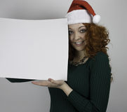 Bärande jultomtenhatt för ung kvinna som rymmer det tomma tecknet Royaltyfri Fotografi