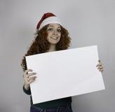 Bärande jultomtenhatt för ung kvinna som rymmer det tomma tecknet Arkivfoton